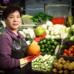 A greengrocer preparing her stall in Tai Yuen Market, Hong Kong